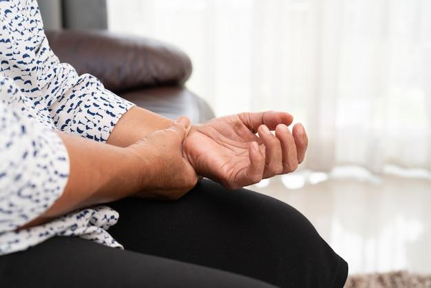 Старая женщина, страдающая от боли в руке, концепция проблемы со здоровьем Premium Фотографии