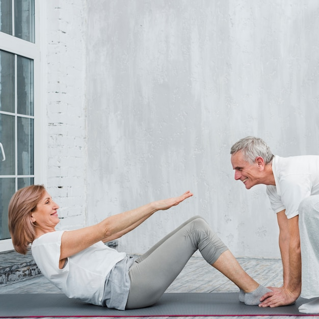 Old woman with her husband doing sit ups in living room Free Photo