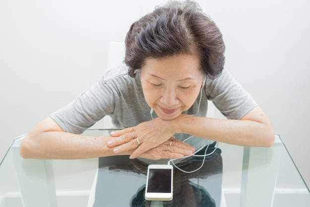Old women  listening to music from mobile Premium Photo