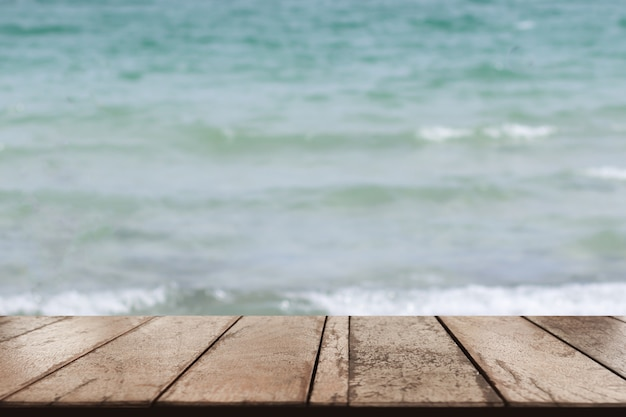Old wood table top on blurred beach background, summer concept Premium Photo