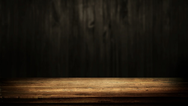 Old wood table with dark brown wall blurred background. Premium Photo