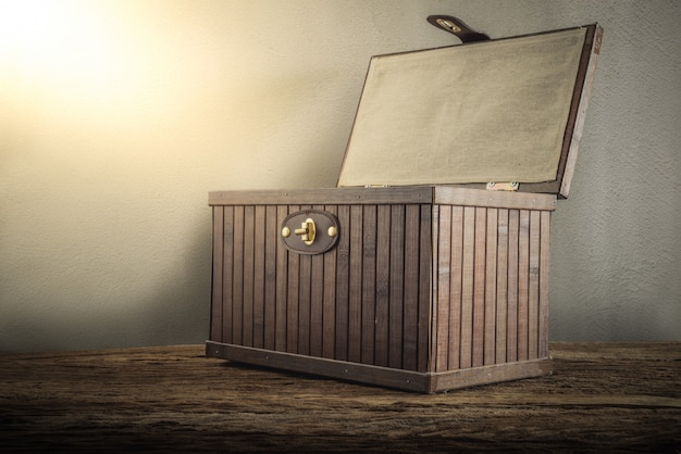 Old wooden chest with open lit on wooden tabletop against grunge wall Premium Photo