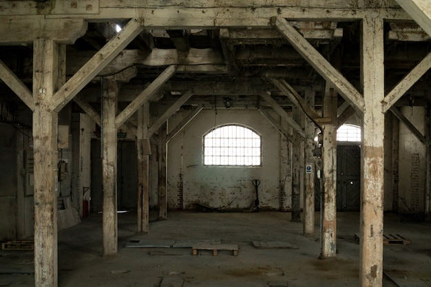 Old wooden columns. old abandoned warehouse, illuminated by light from the window. Premium Photo