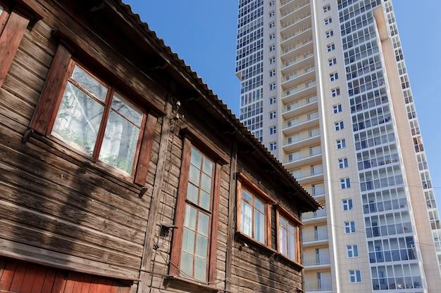 新しい高層ビルを背景にした古い木造住宅 Premium写真