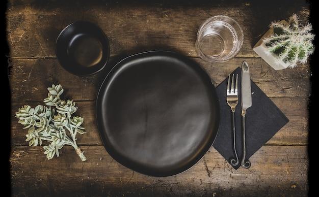 皿の下で、ライトの下で装飾が施された古い木製のテーブル 無料写真