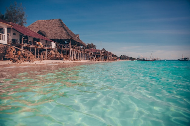 Old wooden tropical bungalow on tropical beach in paradise Premium Photo