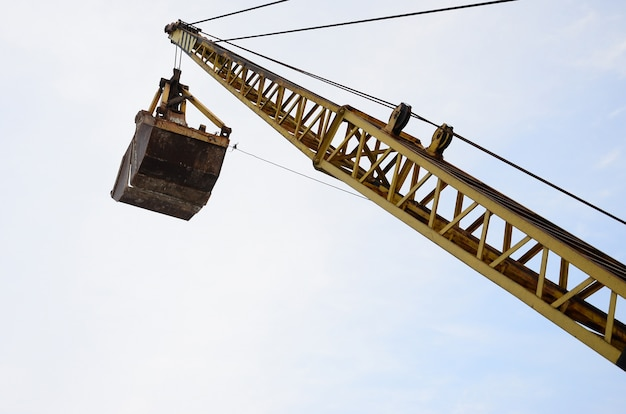 Old yellow mechanical clamshell grab on blue sky background Premium Photo