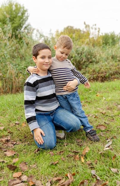Старший брат обнимает младшего. братская любовь. маленькие братья обнимаются и смеются. любовь, доверие и нежность. два мальчика весело вместе на открытом воздухе. счастливая семья. понятие дружбы. Premium Фотографии