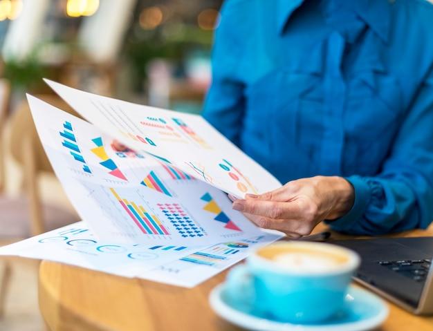 一杯のコーヒーをしながら紙を扱う古いビジネス女性 無料写真