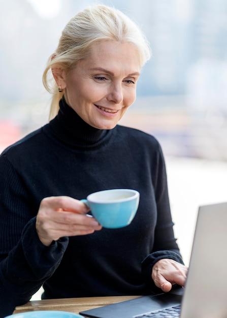 Пожилая деловая женщина, наслаждаясь кофе на открытом воздухе во время работы на ноутбуке Бесплатные Фотографии