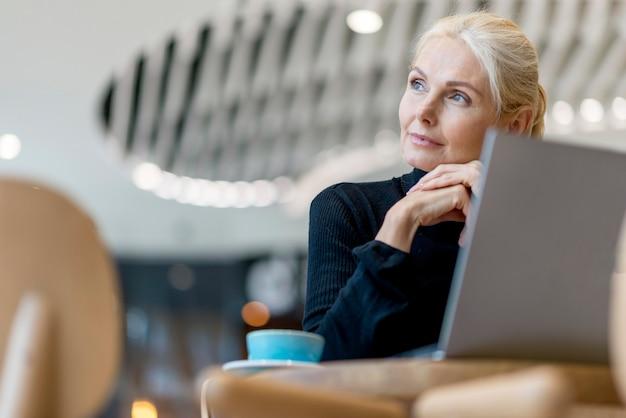 Пожилая деловая женщина пьет кофе и работает на ноутбуке Бесплатные Фотографии