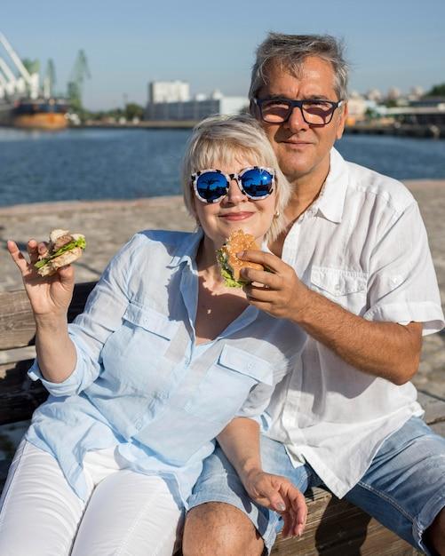 Пожилая пара, наслаждаясь гамбургером на открытом воздухе вместе Бесплатные Фотографии