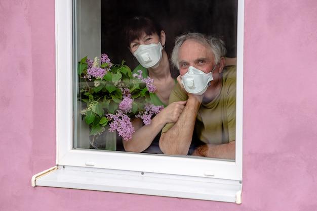 Пожилая пара обнимаются. любящая женщина и мужчина смотрят в окно в масках, ожидая конца самоизоляции. концепция коронавируса карантинного пребывания дома и социальной дистанции. Premium Фотографии