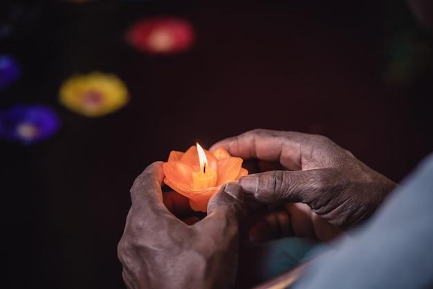 Пожилые руки держат при свечах и молятся за хорошую жизнь и мир людей Premium Фотографии