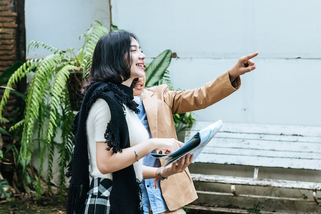 Старшая сестра, держащая карту, молодой брат, указывая вперед. туристический поисковый отель Premium Фотографии