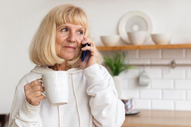 Donna anziana a casa a parlare al telefono mentre beve il caffè Foto Gratuite