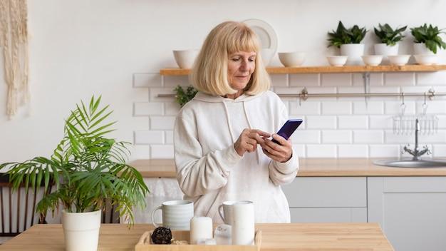 Donna anziana a casa utilizzando smartphone Foto Gratuite