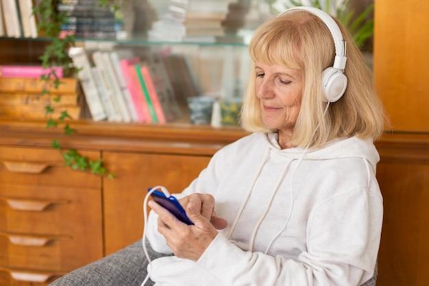 Donna anziana che ascolta la musica a casa utilizzando smartphone e cuffie Foto Gratuite