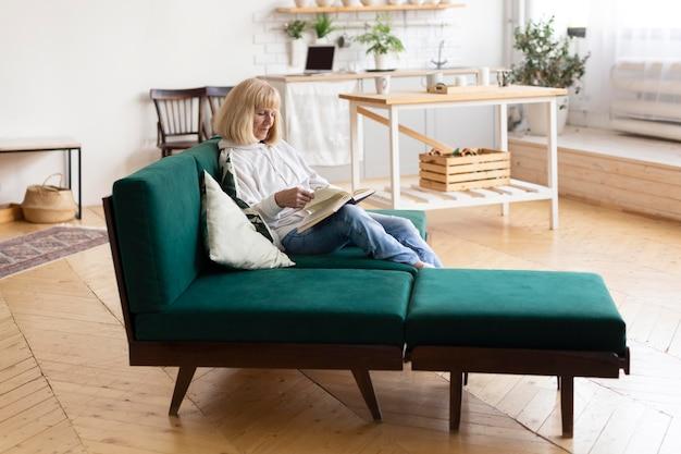 Donna anziana che legge un libro a casa sul divano Foto Gratuite