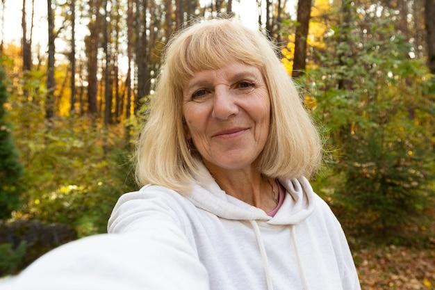 Donna anziana che prende un selfie all'aperto nella natura Foto Gratuite