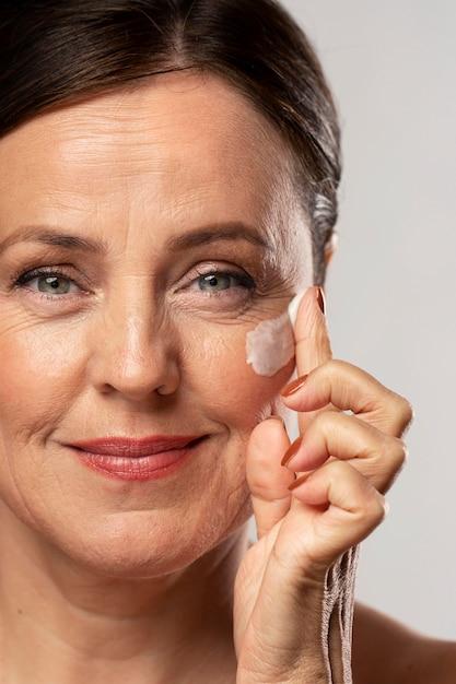 Пожилая женщина использует увлажняющий крем на лице Бесплатные Фотографии