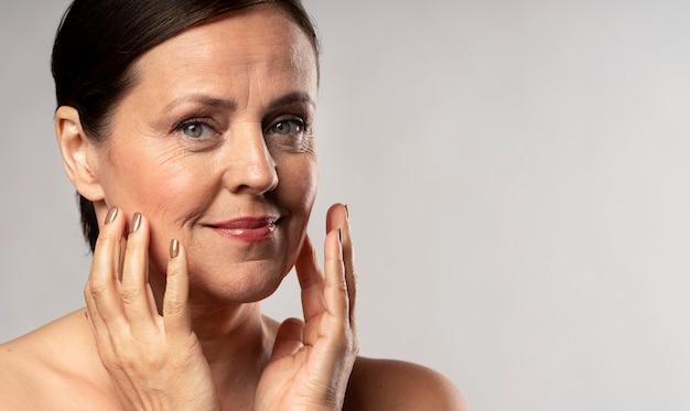 Donna anziana con trucco in posa con le mani sul viso e copia spazio Foto Gratuite