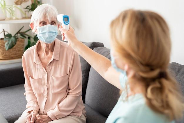Donna anziana con mascherina medica che ottiene la sua temperatura controllata dall'infermiera Foto Gratuite