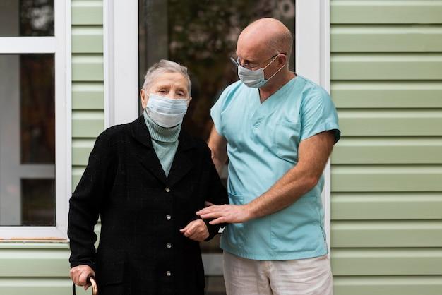 그녀의 남자 간호사의 도움을받은 의료 마스크를 든 노인 여성 프리미엄 사진