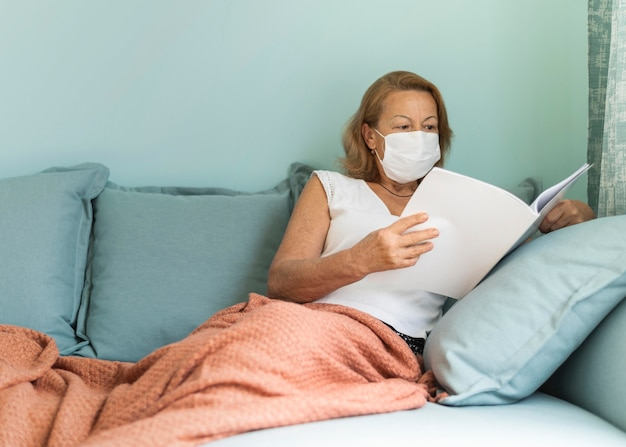 Older woman with medical mask at home during the pandemic reading a book Free Photo