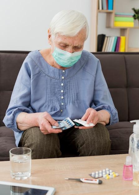 彼女の薬を服用している医療マスクを持つ古い女性 無料写真