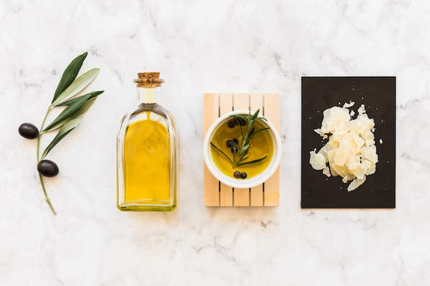 Olive and black pepper oil in bowl and bottle with cheese on white marble backdrop Free Photo