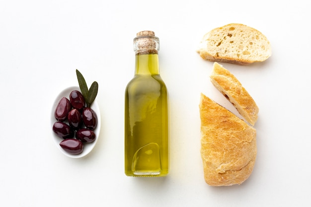 Olive oil bottle bread and purple olives Free Photo