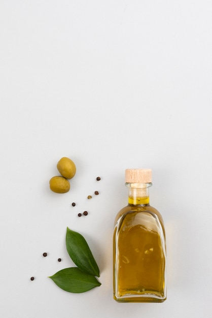 Olive oil bottle on table with copy-space Free Photo