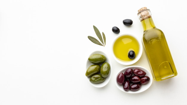 Olive oil bottle with leaves and green purple olives with copy space Premium Photo