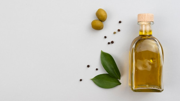 Olive oil bottle with leaves and olives on table Free Photo