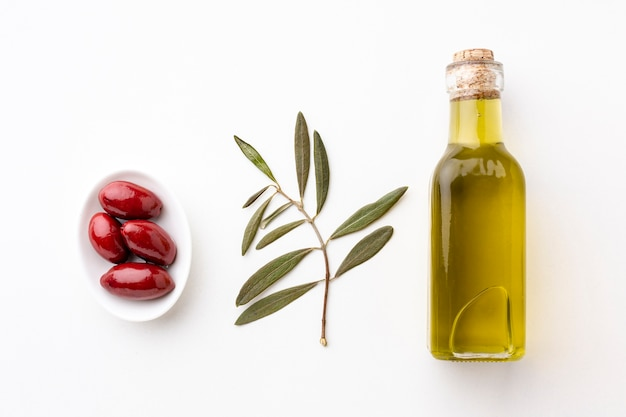 Olive oil bottle with leaves and red olives Free Photo