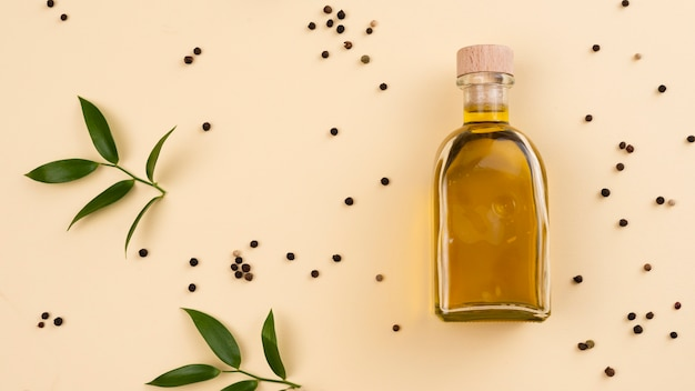 Olive oil bottle with leaves next on table Free Photo