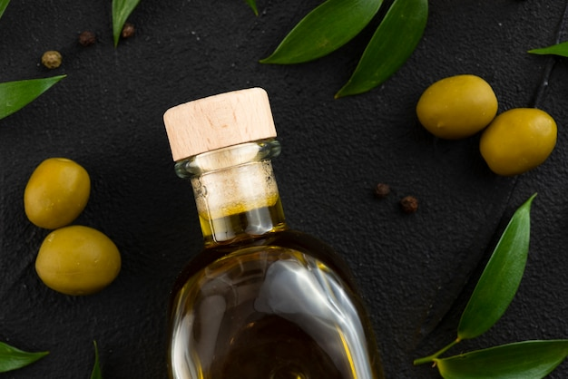 Olive oil bottle with olves and leaves next Free Photo