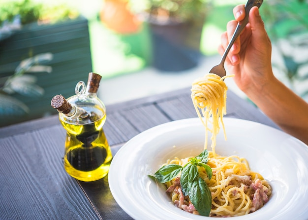 Olive oil bottle with a person holding spaghetti with fork Free Photo