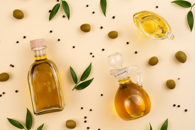 Olive oil in bottles and cup on table Free Photo
