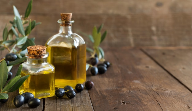 Olive oil and fresh olives on wood table Premium Photo