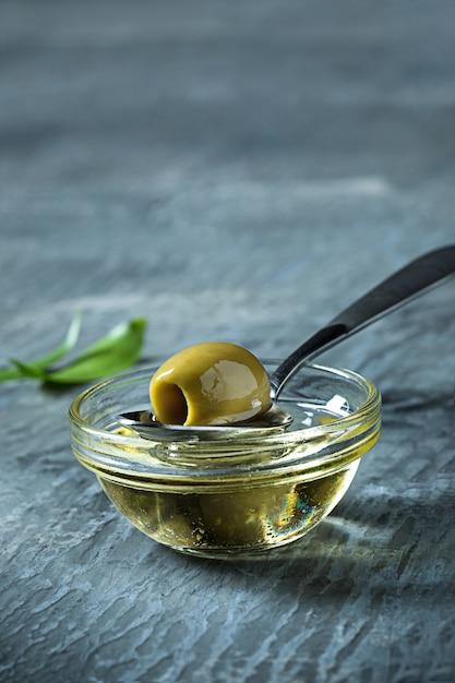 Olio d'oliva e ramo di ulivo sulla tavola di legno Foto Gratuite