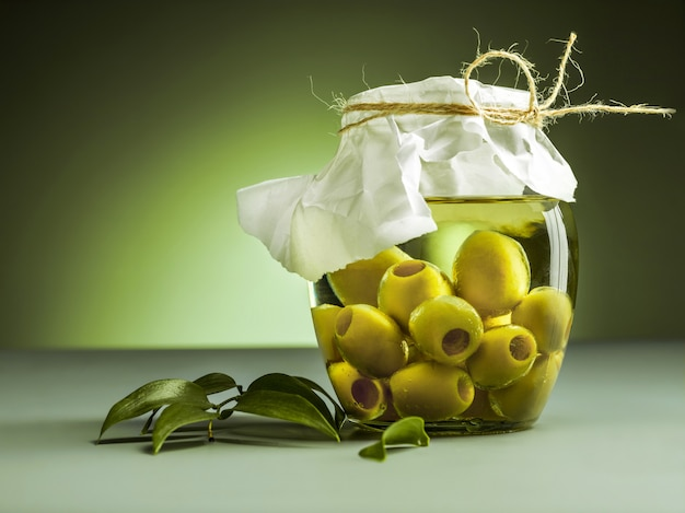 Olive oil and olive branch on wooden table Free Photo