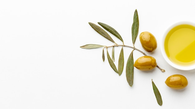 Olive oil saucer with leaves and yellow olives with copy space Free Photo