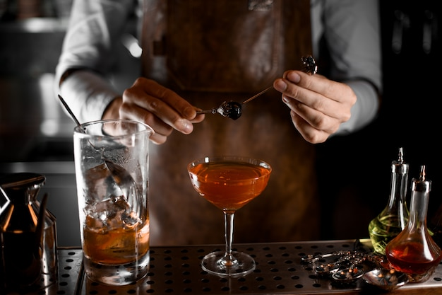 An olive on skewer in bartender's hands Premium Photo