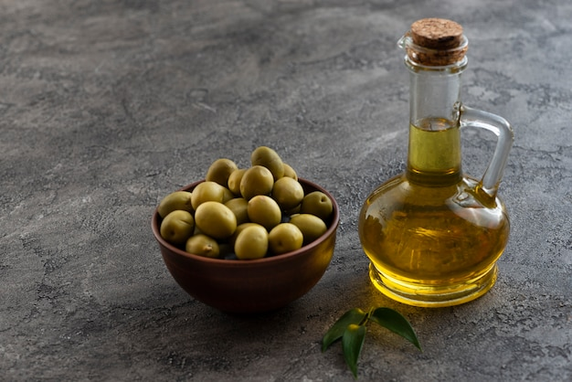Olives in a bowl and nearby oil bottle Free Photo