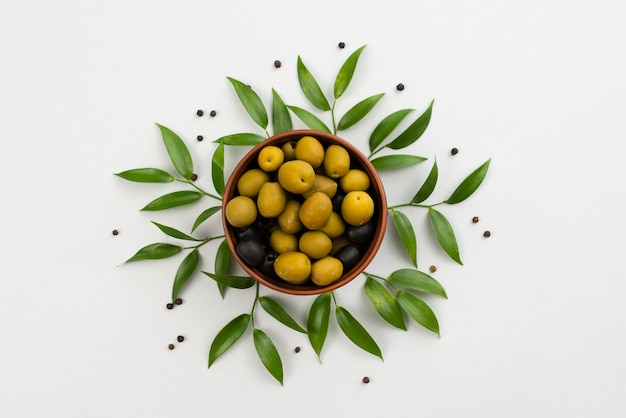 Olives in bowl with leaves next on table Premium Photo