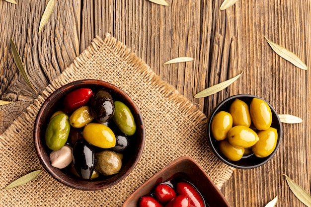 Olives in bowls and leaves on textile material Free Photo