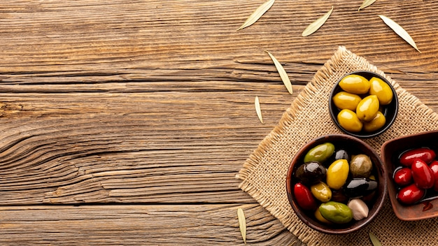 Olives in bowls on textile material with copy space Free Photo