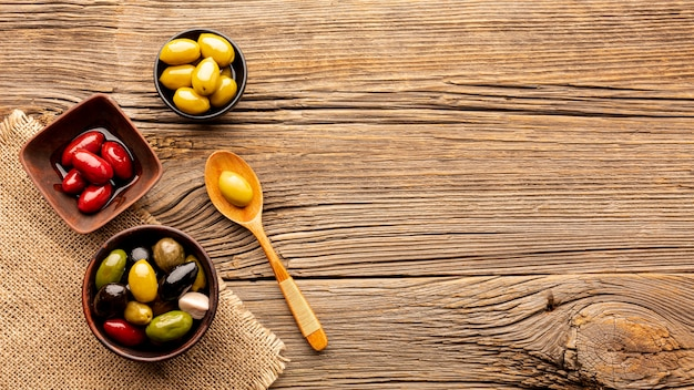 Olives in bowls and wooden spoon with copy space Free Photo